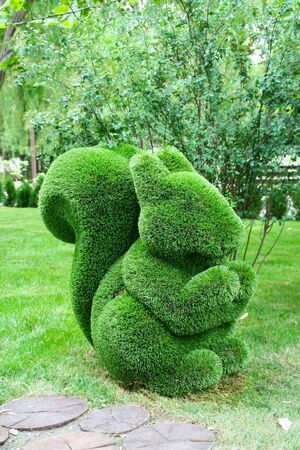 Picturesque green squirrel made of artificial grass green against the background of trees.
