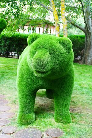 Green bear made of artificial grass green on the background of trees. Stock fotó
