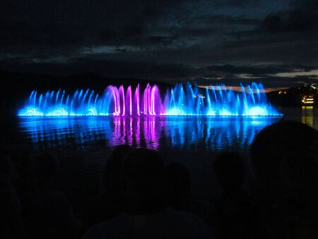 Night photo of fountains of different colors.