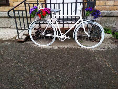 A vintage two-wheeled Bicycle with flowers on it.