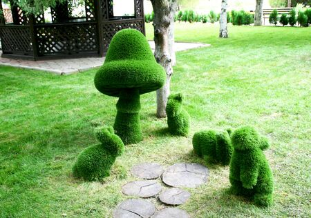 Sculptures of bunnies and a mushroom made of green polymer grass in the Park. Stock fotó