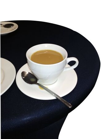 White Cup and saucer and coffee with milk on a black table.