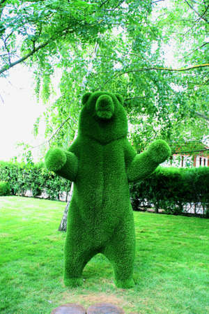 Sculpture of a bear made of plastic fur under the branches of green trees on the background of a green Park.