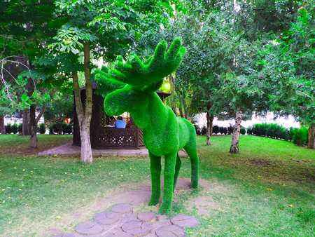 Sculpture of a standing moose in close-up made of artificial green coating. Stock fotó