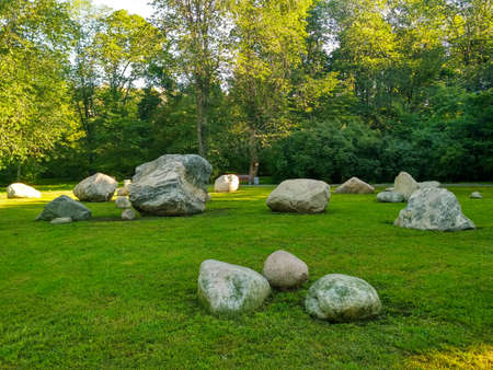 Summer landscape of stones on the green grass in the Park.