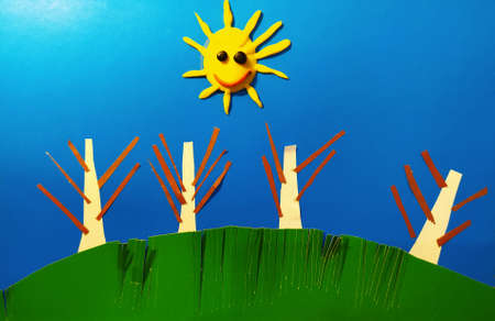 Illustration of the sun with trees on a green hill against a blue sky made of paper strips.