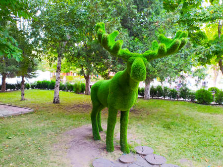 Figure of a deer with green faux fur horns in the Park.
