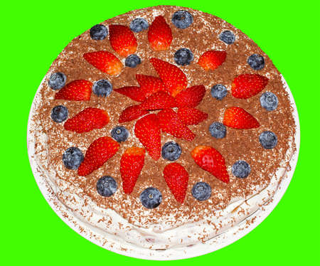 Round cake on a green background with strawberries and blueberries.