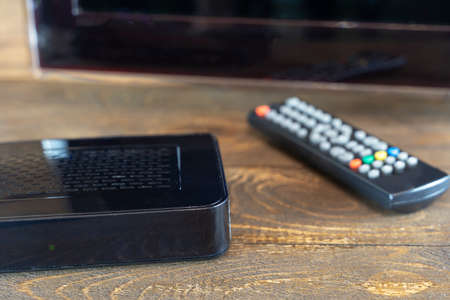 TV set-top box on a wooden background in