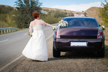bride and car, bride in a white dress with a bouquet near the wedding car