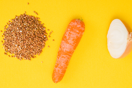 brown buckwheat beans, onion cut in half, carrots on a yellow background Stock fotó