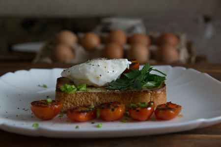 poached egg, boiled egg on toast with herbs and tomatoes Stock Photo