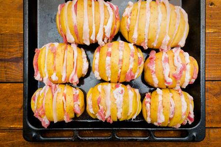 오븐에서 요리하기 위해 베이컨을 곁들인 노란색 얇게 썬 감자 스톡 콘텐츠