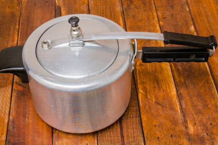 aluminum pressure cooker with black plastic handles on a wood background