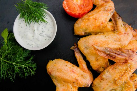 fried chicken wings on a plate with garlic sauce Stock Photo