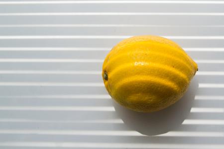 lemon on the windowsill lit with window stripes