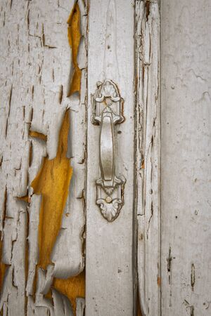 the door handle is painted silver. Old door with peeling paint. vintage textured background for design