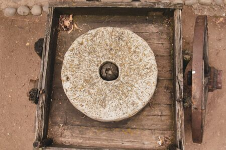 device for the manufacture of flour of the old type. stone millstones on a wooden platform. ancient wheelbarrow on wooden wheels Stock Photo