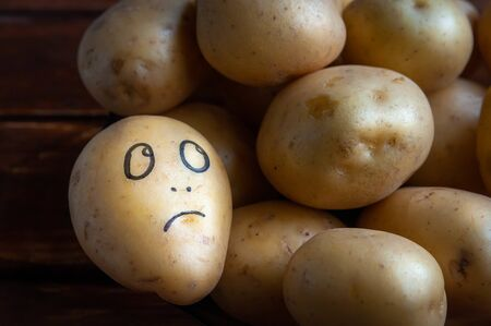 a potato with a painted face lies on a plate. concept of dissent rejection and loneliness