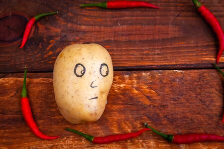 the potato is surrounded by very hot red pepper .Concept of very spicy food, heartburn, and pancreatic problems