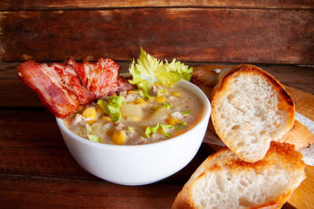 Corn chowder soup with bacon. Brown wooden background. Close-up view Banco de Imagens