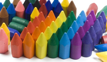 Rainbow stacked wax crayons on colored background photo