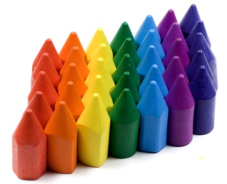 Rainbow stacked wax crayons on white background photo