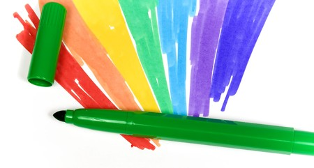 removed: Dark green felt-tip pen with removed cap on a background of the drawn rainbow close-up Stock Photo