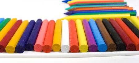 Many wax pencils on a white plastic board close up photo