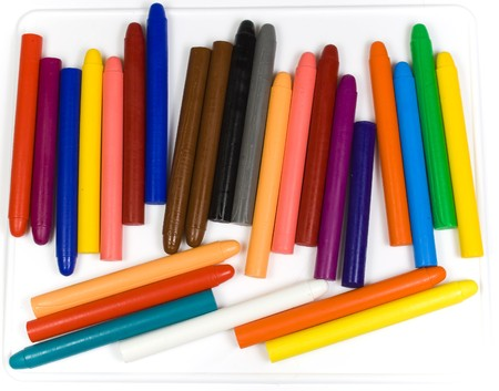 Childrens oil pencils spread out to white plastic photo