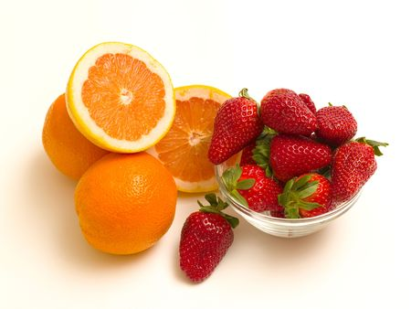 a pile of oranges with strawberries on white background Stock Photo