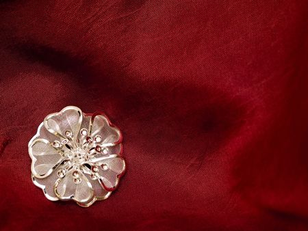 broach: silver broach on silky background pearly folded