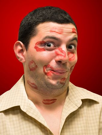 passionate kiss: man portrait with many kisses on his face Stock Photo
