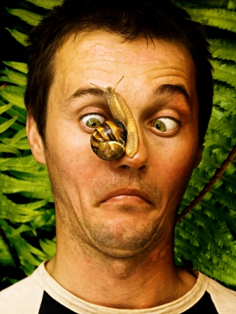 weerzinwekkend: man met kruipende slak op zijn gezicht Stockfoto