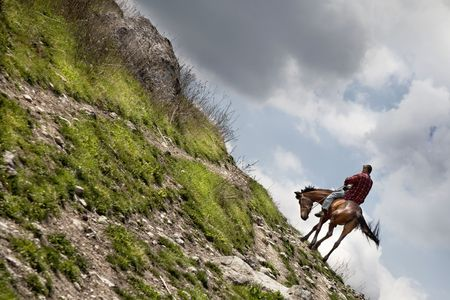 cowboy on a horse riding up the hill