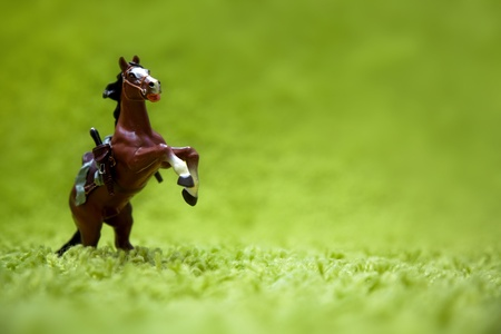 miniature toy horse in running posture on a carpet like grass