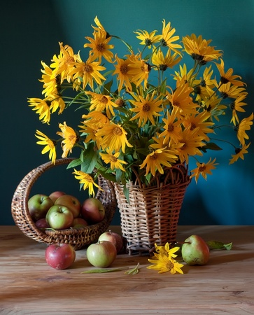 still life with yellow flowers and apples
