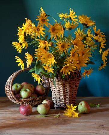 Stilleven met gele bloemen en appels