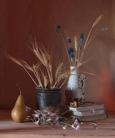 still life with grain and dried flowers in a vase photo