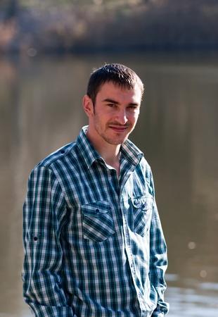 Jonge knappe positieve man in casual kleding glimlachen Stockfoto