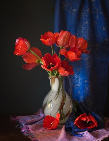 small purple flower: red tulips in a vase