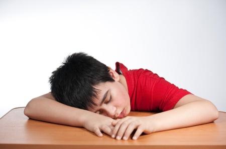 jongen doet zijn saai huiswerk en slapen Stockfoto