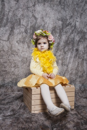 Young girl sitting on a stool photo