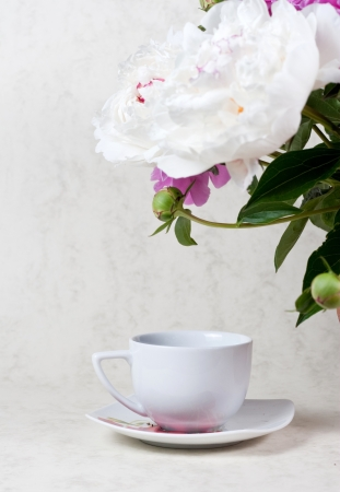 A cup of tea and peony on wooden table photo
