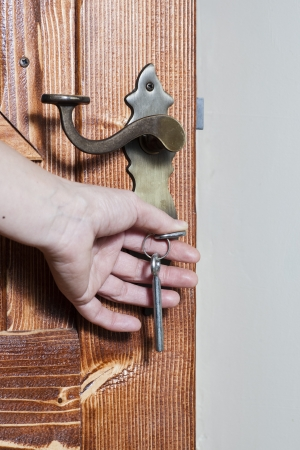 Opsluiten of ontgrendelen deur met sleutel in de hand Stockfoto