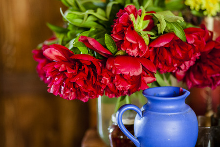 Pink peonies in vase on wood background photo