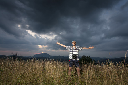Teenager boy  standing on top of a mountain with raised hands photo