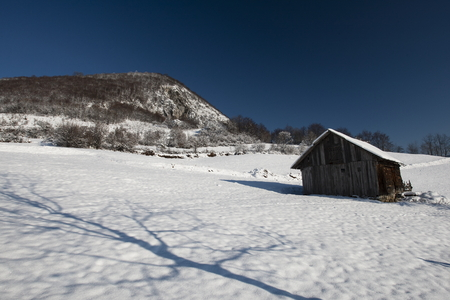 Old farm in the mountains at winter photo