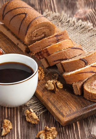 Tasty cake roll and cofee on old wooden table. Rustic style Stock Photo