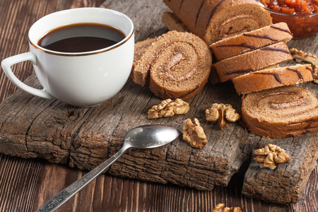 Tasty cake roll and cofee on old wooden table. Rustic style Zdjęcie Seryjne
